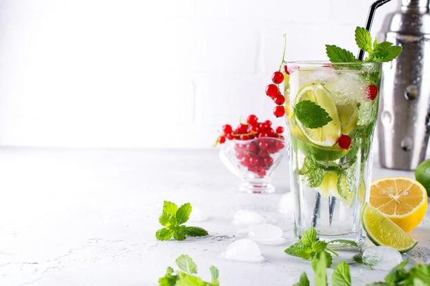 Frio verão caseiro frutas e bagas limonada. mojito, limonada ou sangria em vidro. copie o espaço