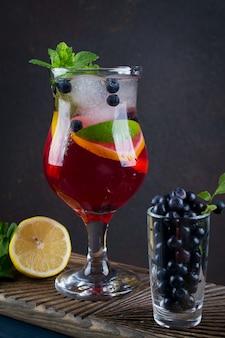 Frio verão caseiro frutas e bagas limonada. mojito, limonada ou sangria em vidro. em fundo escuro