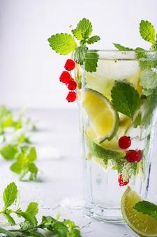 Frio verão caseiro frutas e bagas limonada. mojito, limonada ou sangria em vidro.