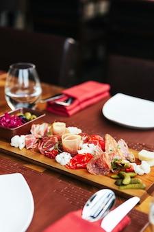 Frios na placa de madeira com presunto, bacon, salame e salsichas. aperitivos de prato de carne servidos com picles e azeitonas na mesa de jantar com talheres.
