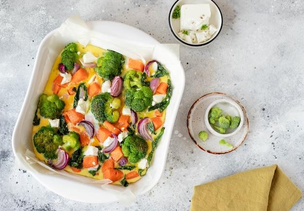 Fritada com abóbora, brócolis e queijo feta em um prato branco. vista do topo