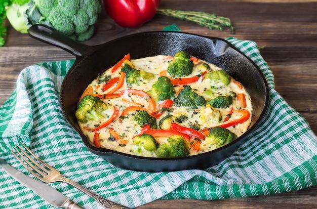 Fritada com brócolis e pimenta vermelha na frigideira de ferro sobre fundo de madeira rústica com ingredientes.