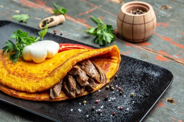 Fritada com carne e ovo escalfado. omelete assado na mesa escura. gorduras saudáveis, alimentação limpa para perda de peso