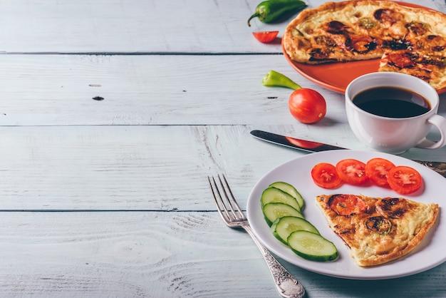 Fritada com chouriço, tomate e pimenta no prato e café.