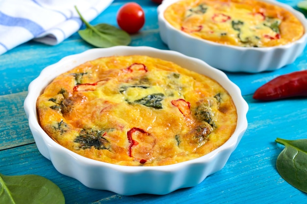 Fritada com legumes frescos e espinafre. omelete italiano em formas de cerâmica sobre um fundo azul de madeira.
