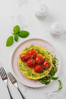 Fritada com rúcula, batata e tomate cereja em panela de ferro na velha mesa de pedra. vista do topo.