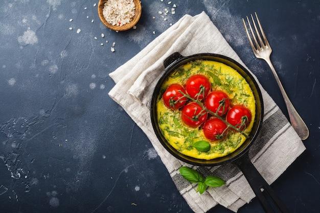 Fritada com rúcula, batata e tomate cereja em panela de ferro na velha mesa de pedra.