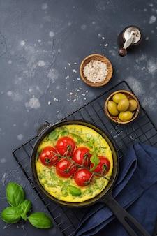 Fritada com rúcula, batata e tomate cereja em panela de ferro no fundo da mesa de pedra velha.