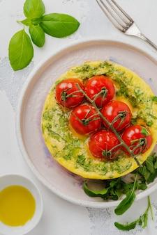 Fritada com rúcula, batata e tomate cereja em uma frigideira de ferro no fundo da velha mesa de pedra
