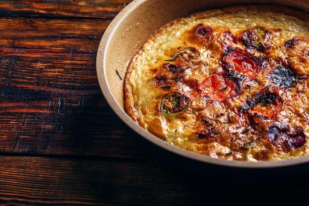 Fritada cozida com chouriço, tomate e pimenta numa frigideira sobre fundo escuro de madeira. visão de alto ângulo.
