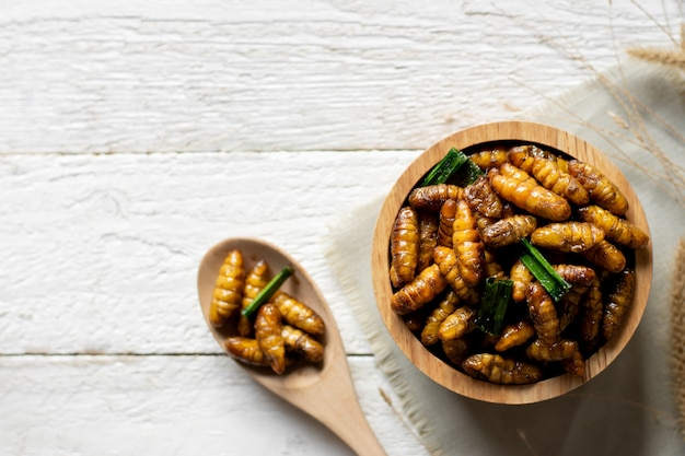 Fritando insetos em uma tigela colocada sobre uma mesa de madeira branca, comida saudável de proteína.