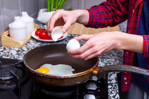 Fritar caseiros, ovos de galinha na frigideira na cozinha em casa
