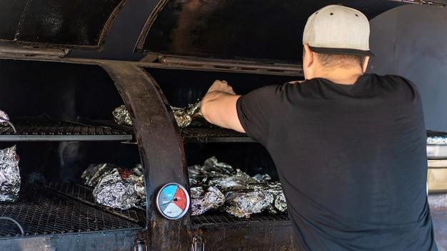 Fritar frangos em papel alumínio em uma grelha, cozinheiro de trabalho. bbq. comida de rua