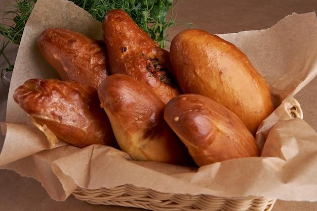 Fritas tortas russas ou ucranianas em uma cesta em uma mesa rústica com cebola, pimenta, farinha
