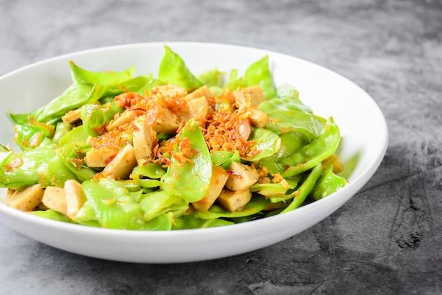 Frite as ervilhas com salsicha de porco grelhada vietnamita, com cobertura de chalotas e alhos fritos crocantes