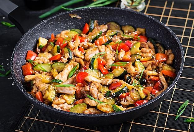 Frite com frango, abobrinha e pimentão - comida chinesa.