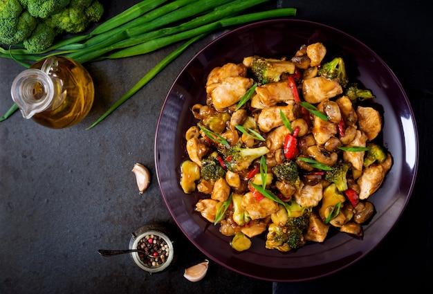 Frite com frango, cogumelos, brócolis e pimentão - comida chinesa. vista do topo