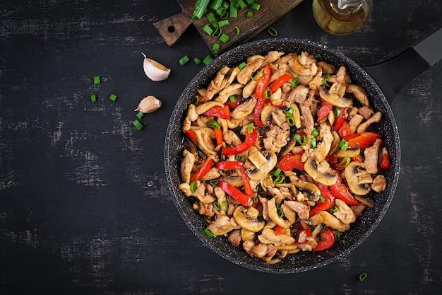 Frite com frango, cogumelos e pimentão - comida chinesa. vista superior, acima