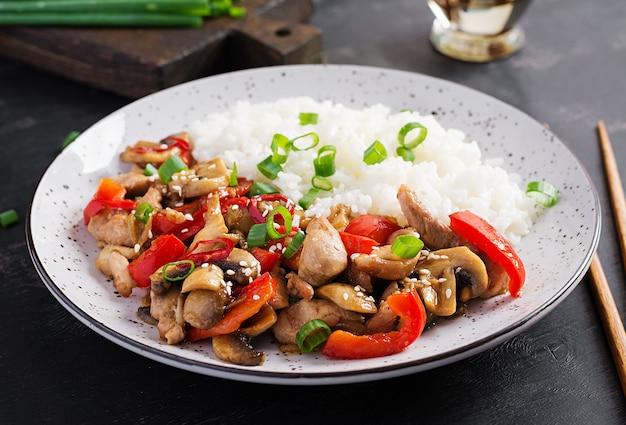 Frite com frango, cogumelos, pimentão e arroz cozido. comida chinesa.