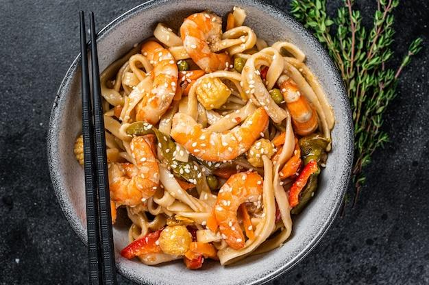 Frite macarrão udon de frutos do mar com camarões em uma tigela. preto