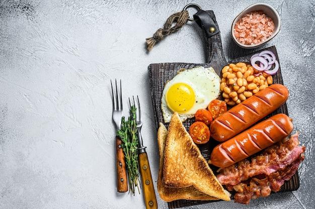 Frite o café da manhã inglês completo com ovos fritos, linguiça, bacon, feijão e torradas em uma tábua de madeira.