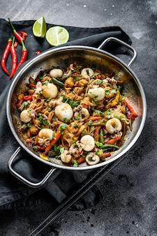 Frite o macarrão com frutos do mar e legumes em uma panela wok. superfície preta. vista do topo