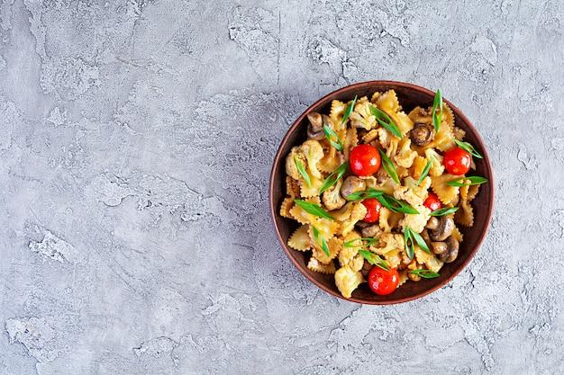 Frite o macarrão com legumes, couve-flor e cogumelos. vista do topo