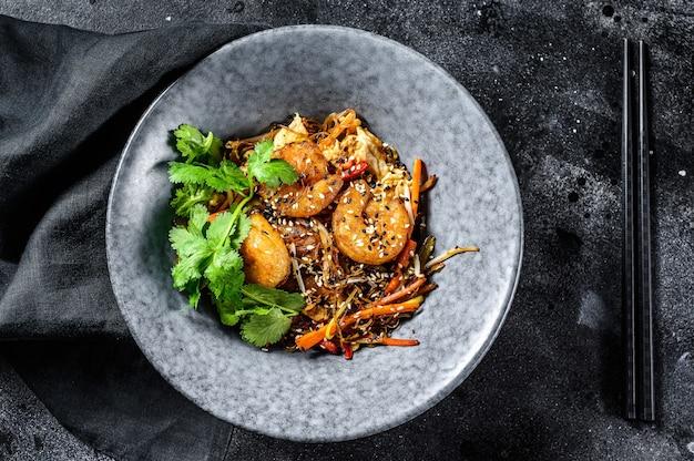 Frite o macarrão de arroz com camarões e vegetais. asia wok