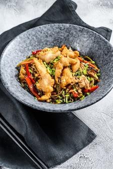 Frite o macarrão de vidro com filé de frango e legumes.