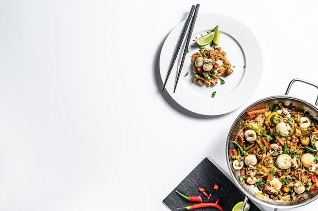 Frite o macarrão udon com frutos do mar e legumes. fundo branco. vista do topo. copie o espaço