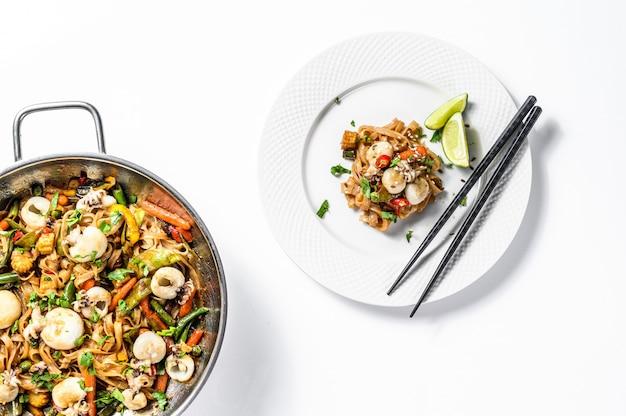 Frite o macarrão udon com frutos do mar e legumes. fundo branco. vista do topo