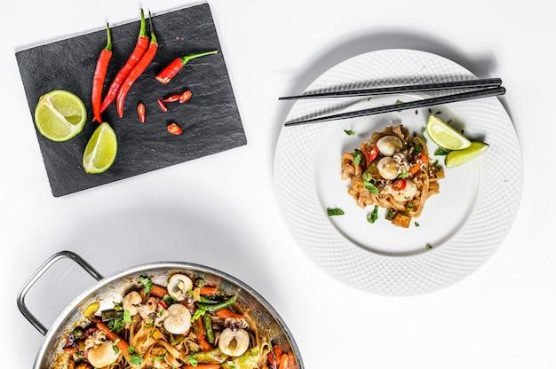 Frite o macarrão udon com frutos do mar e legumes.