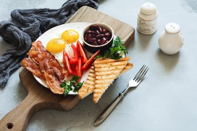 Frite o tradicional café da manhã inglês com ovos fritos, salsichas, bacon, morcela, feijão, torradas e chá no fundo cinza de concreto. vista do topo