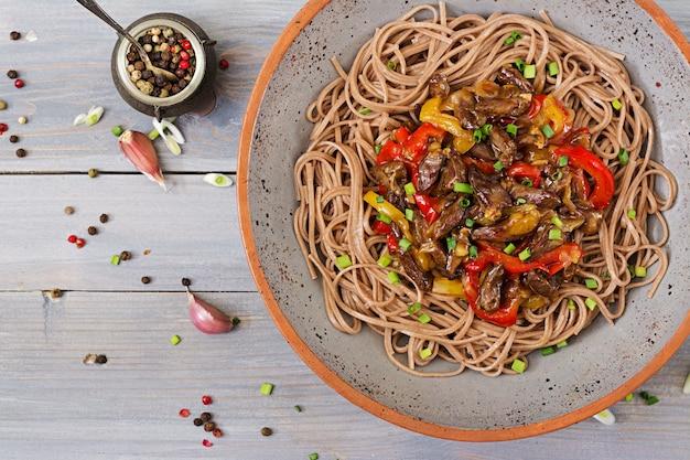 Frite os corações de frango, pimentão, cebola e macarrão de trigo sarraceno. vista do topo