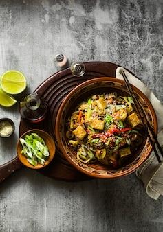 Frite vegan asiática com tofu, macarrão de arroz e vegetais, vista de cima.