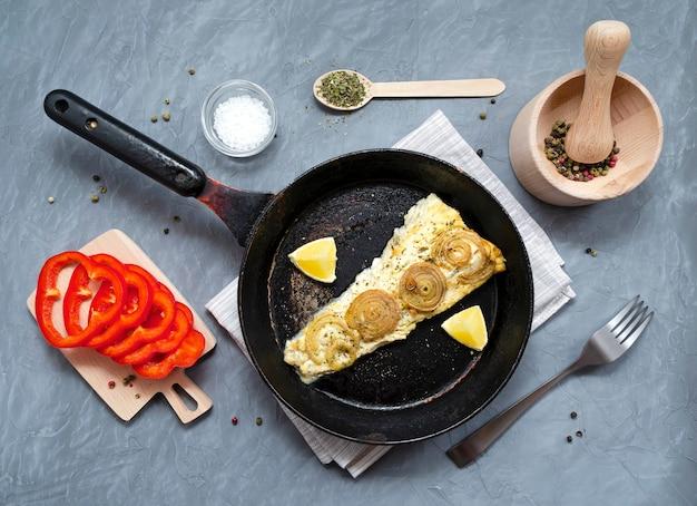 Frito assado cavala trachurus com cebola e ervas secas em uma frigideira velha com uma toalha e um garfo.