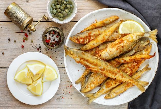 Frito cheirava em um prato branco, peixe pequeno, alcaparras, limão, pimenta e sal em uma mesa de madeira