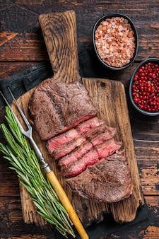 Frito top blade ou bifes de carne de rosbife na placa de madeira com alecrim. fundo de madeira escuro. vista do topo.