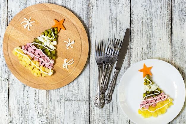 Fromsalad da árvore de natal mais olivier no prato sobre uma mesa de madeira branca. vista do topo