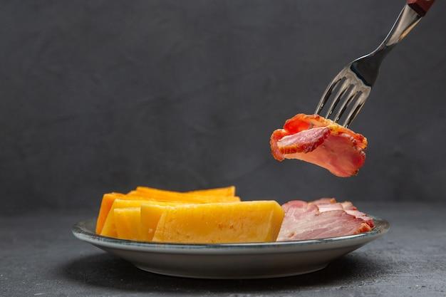 Fron vista de perto a mão pegando uma comida com um garfo em um prato azul com deliciosos petiscos em um fundo preto