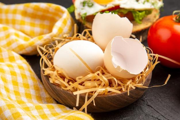 Frontal close view ovo de galinha fresco com sanduíche de ovo e tomate no fundo escuro foto comida refeição café da manhã animal chá cor fazenda manhã