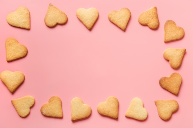 Fronteira de biscoitos em forma de coração caseiro em rosa. postura plana.