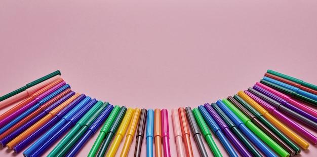 Fronteira de canetas de ponta de feltro coloridas no pano de fundo rosa com lugar para texto. vista do topo