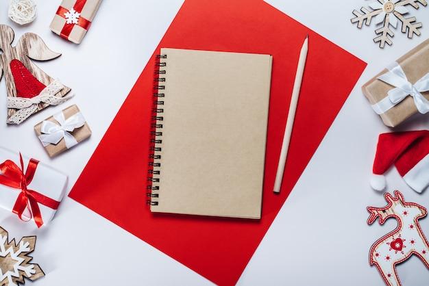 Fronteira de decorações do feriado, brinquedos e caderno de papel ofício em branco. composição de natal. vista superior, configuração plana.