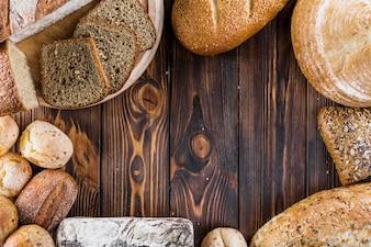 Fronteira de diferentes pães assados sobre o cenário de madeira