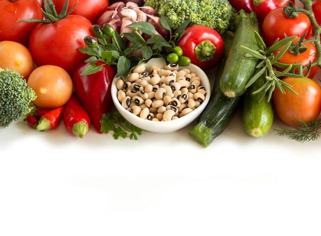 Fronteira de ervilhas e legumes de olhos pretos crus, isolada no branco close-up