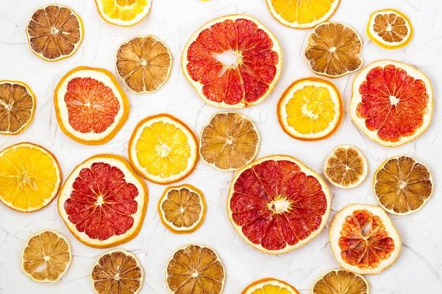 Fronteira de fatias secas de várias frutas cítricas em fundo branco. copos de laranja limão toranja