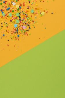 Fronteira de granulado decorativo em fundo amarelo e verde. blocos de cores. multicolor açúcar em pó de confeitaria no canto. paus de açúcar doce dispersos, estrelas e bolas. copie o espaço.