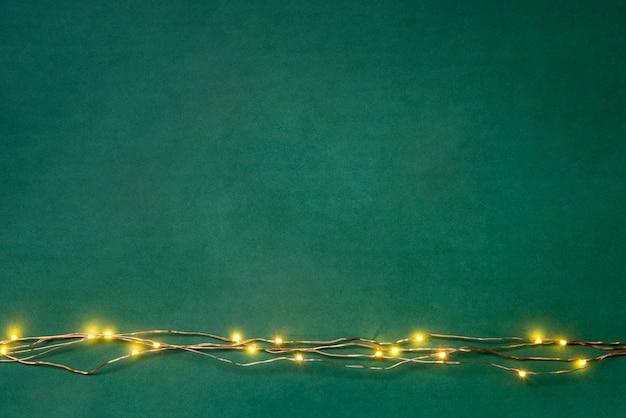Fronteira de guirlanda de luzes de natal sobre fundo verde.