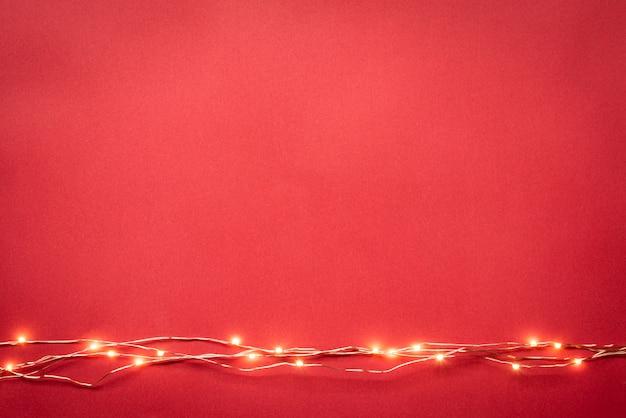 Fronteira de guirlanda de luzes de natal sobre fundo vermelho.